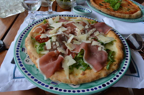 Fresh, wood-fired pizza with proscuitto, mozzarella, arugula, and shaved parmesan, topped with basil picked right from their garden.